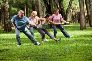 Multi-ethnic group of adults practicing tai chi in park. Main focus on Asian woman.
