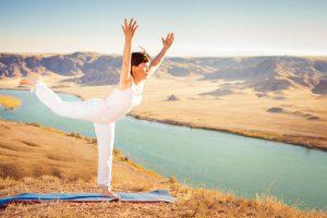 Inspired asian woman doing exercise of yoga at mountain range of Kazakhstan. She dressed in white sportswear.